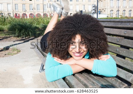 Young beautiful American woman lying on a bench in the city