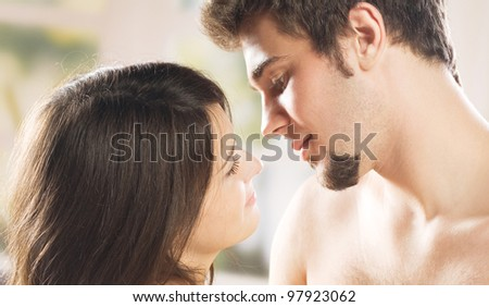 Young beautiful amorous couple at bedroom