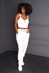 Young beautiful and fashionable african woman with afro hair, wearing sporty comfy clothes, posing over dark studio background.