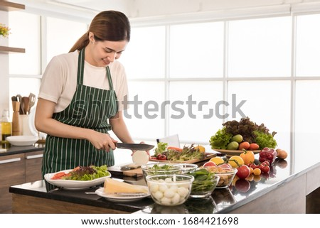 Young, beautiful and friendly face girl smile wearing appron cooking in loft style kitchen among fresh ingredients and showing how to cut and prepare vegetables to make a dish of vegetable salad. Foto stock ©