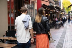 Young beautiful and handsome couple walking on the street looking for restaurant for breakfast