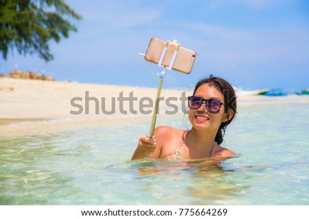 young beautiful and happy Asian Chinese woman having fun on sea water taking selfie picture with mobile phone camera on paradise beach water smiling in holiday and vacation concept