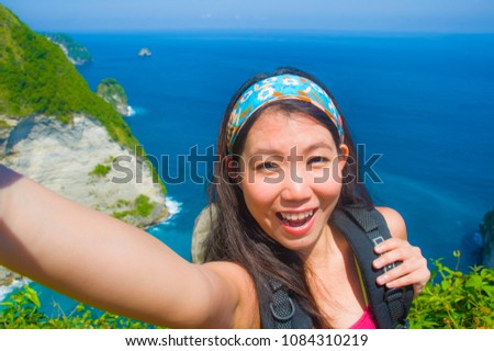 young beautiful and happy Asian Korean tourist woman taking selfie picture smiling carrying backpack after hiking excursion on top of tropical sea cliff landscape in holidays travel destination