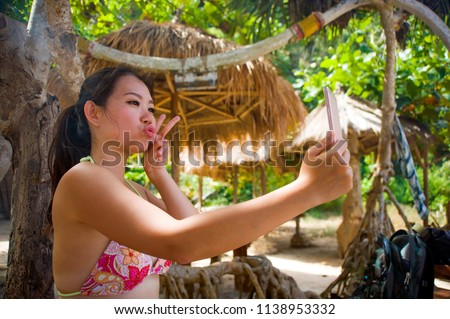 young beautiful and happy Asian Korean woman taking self portrait selfie with mobile phone at tropical paradise beach resort under palm trees shade enjoying summer holidays travel