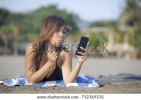 young beautiful and happy Asian woman using mobile phone taking selfie portrait photo having fun relaxed on beach sand having suntan enjoying tropical holiday and vacation