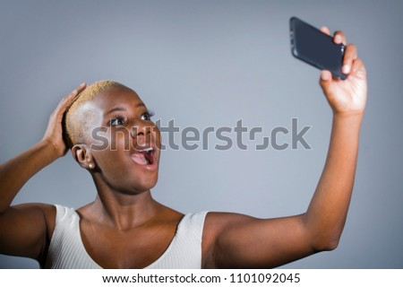 young beautiful and happy black afro American woman excited taking selfie picture portrait with mobile phone or recording self portrait video posing showing proud her shaved head hair style