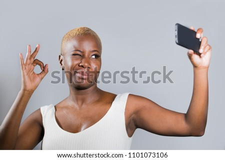 young beautiful and happy black afro American woman smiling excited taking selfie picture portrait with mobile phone or recording self portrait video posing cheerful having fun giving ok fingers