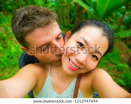 young beautiful and happy mixed ethnicity couple beautiful Asian Korean woman and white man in love taking selfie picture outdoors enjoying romantic holidays trip in tropical honeymoon vacation