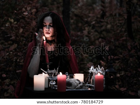 Stock Photo Young beautiful and mysterious Witch woman Provide Dark Ritual in woods With Detached Heart and Candles
