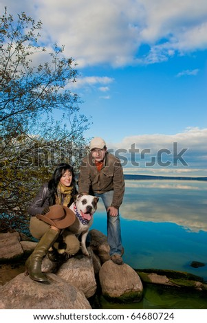 young beautiful and pretty looking caucasian family standing together on a big stone near a water line of sea having their white big dog near them with mirror water reflection.shoot made on location