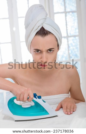 Young beautiful and tired woman or housewife wrapped with a white towel ironing clothes at home. Hard and boring housework