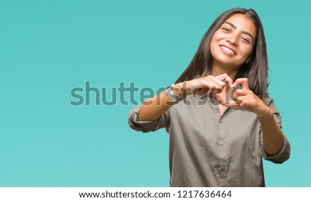 Young beautiful arab woman over isolated background smiling in love showing heart symbol and shape with hands. Romantic concept.