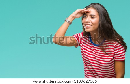 Young beautiful arab woman over isolated background very happy and smiling looking far away with hand over head. Searching concept.