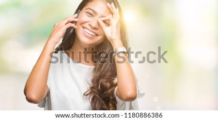 Young beautiful arab woman talking on the phone over isolated background with happy face smiling doing ok sign with hand on eye looking through fingers #1180886386