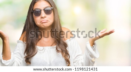 Young beautiful arab woman wearing sunglasses over isolated background clueless and confused expression with arms and hands raised. Doubt concept. #1198121431