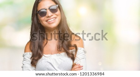 Young beautiful arab woman wearing sunglasses over isolated background happy face smiling with crossed arms looking at the camera. Positive person. #1201336984