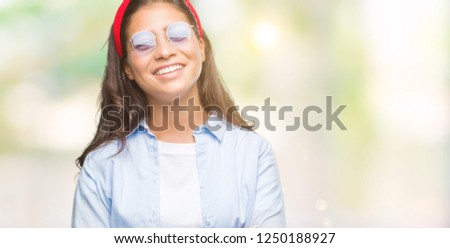Young beautiful arab woman wearing sunglasses over isolated background happy face smiling with crossed arms looking at the camera. Positive person. #1250188927