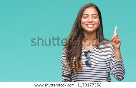 Young beautiful arab woman wearing sunglasses over isolated background showing and pointing up with finger number one while smiling confident and happy. #1170177556