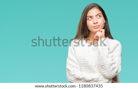 Young beautiful arab woman wearing winter sweater over isolated background with hand on chin thinking about question, pensive expression. Smiling with thoughtful face. Doubt concept.