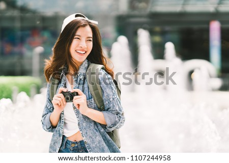 Young beautiful Asian backpack traveler woman using digital compact camera and smile, looking at copy space. Journey trip lifestyle, world travel explorer or Asia summer tourism concept #1107244958