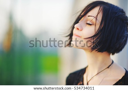 Young beautiful asian brunette woman, eyes closed, enjoying the bright warm day on blurred background close up. Air deep breath, yoga mind zen relax, calm peace pray hope concept. Light skin lady spa.