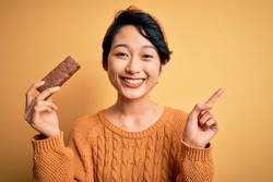 Young beautiful asian girl holding energy protein bar of cereal over isolated yellow background surprised with an idea or question pointing finger with happy face, number one
