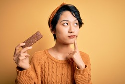 Young beautiful asian girl holding energy protein bar of cereal over isolated yellow background serious face thinking about question, very confused idea
