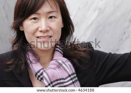 Young Beautiful Asian Girl In Winter Clothes (Coat, Scarf) Standing Next To Large Grey Stones