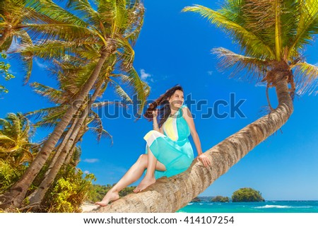 Young beautiful Asian  girl on the palm tree on a tropical beach. Tropical sea in the background. Summer vacation concept. #414107254