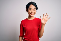Young beautiful asian girl wearing casual red t-shirt standing over isolated white background showing and pointing up with fingers number five while smiling confident and happy.