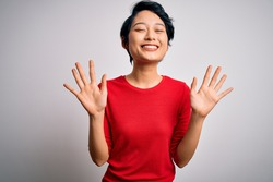 Young beautiful asian girl wearing casual red t-shirt standing over isolated white background showing and pointing up with fingers number ten while smiling confident and happy.
