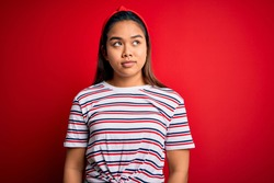 Young beautiful asian girl wearing casual striped t-shirt over isolated red background smiling looking to the side and staring away thinking.
