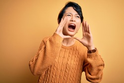 Young beautiful asian girl wearing casual sweater and diadem standing over yellow background Shouting angry out loud with hands over mouth