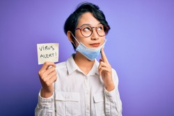 Young beautiful asian girl wearing medical mask holding reminder with virus alert message serious face thinking about question, very confused idea