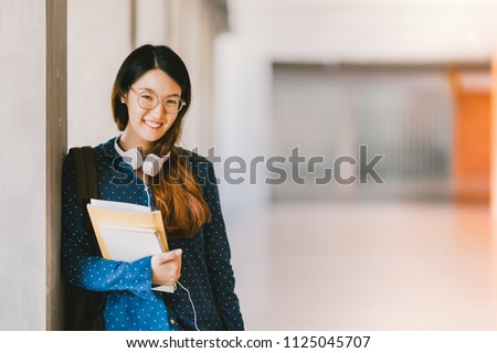Young beautiful Asian high school girl or college student wearing eyeglasses, smiling in university campus with copy space. Education, casual lifestyle, geek or nerd smart people concept