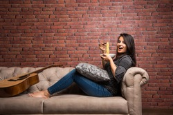 Young beautiful asian/indian girl eating instant noodle using chopsticks while seating at sofa at home, selective focus