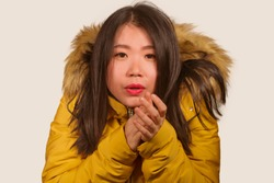 young beautiful Asian Korean woman feeling cold and chilly freezing feeling cold in Winter weather wearing yellow jacket with fur hood isolated on white studio background