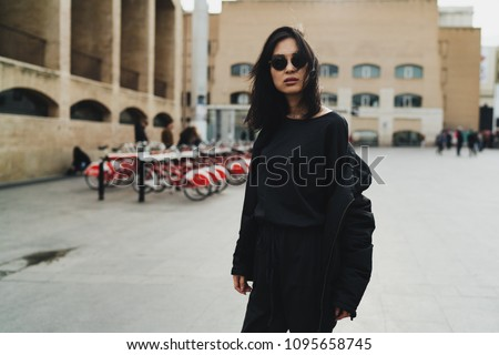 Young beautiful asian model look woman in sunglasses wearing trendy black clothes posing to the camera while standing on a city background. Stylish hipster girl walking the city on a weekend day.