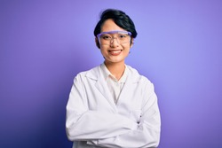 Young beautiful asian scientist girl wearing coat and glasses over purple background happy face smiling with crossed arms looking at the camera. Positive person.