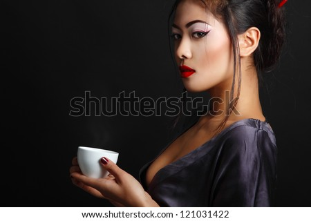 Young beautiful asian woman and tea ceremony, studio shot over black background with copyspace