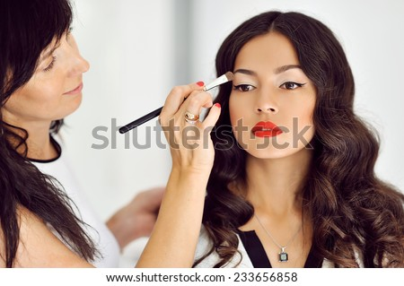 Young beautiful asian woman applying make-up by make-up artist