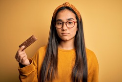 Young beautiful asian woman eating healthy protein bar over isolated yellow background with a confident expression on smart face thinking serious