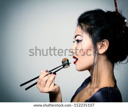 Young beautiful asian woman eating sushi with chopsticks toned image and noise added