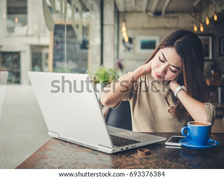 Young beautiful asian woman feeling hurt,fatigue, pain at neck, muscle during working with laptop in coffee shop cafe, stretching arms and body for relaxing, vintage tone, office syndrome concept