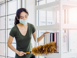 Young beautiful Asian woman, housewife in casual cloth wearing protective face mask cleaning books on bookshelf with feather duster in living room on huge glass window background on sunny day.