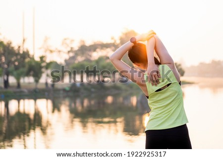 Young beautiful Asian woman in sports outfits doing stretching before workout outdoor in the park in the morning to get a healthy lifestyle. Healthy young woman warming up outdoors.