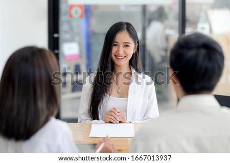 Young beautiful asian woman in white shirt and long hair smiling with happiness at job interview. Young female candidate smiling at job interview.