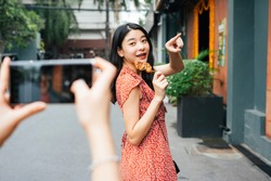 Young beautiful asian woman on red dress eating street food infront of smartphone camera. Food blogger. Street food vlogger.