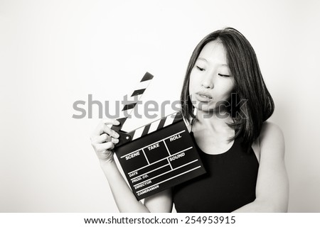 Young beautiful asian woman portrait, black dress, looking at  clapperboard, in black and white #254953915