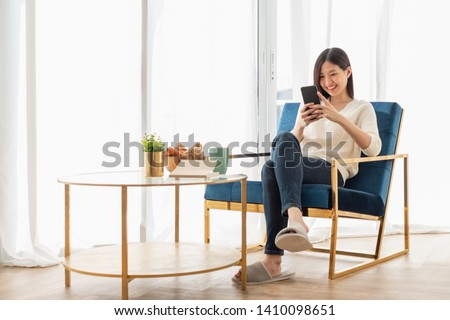 Young beautiful Asian woman relaxing in living room at home, reading books, drinking coffee and using phone in the morning with happy feeling